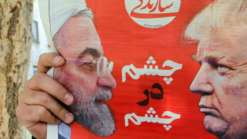 IRAN -- An Iranian man reads the Iranian daily newspaper 'Sazandegi' with a pictures of Iranian president Hassan Rohani and U.S. President Donald Trump on its front page and the title reading in Persian 'Eyes to Eyes', in Tehran, April 9, 2019
