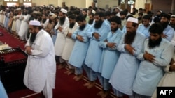 In this handout photograph released by Jamaat-ud-Dawa on July 30, Hafiz Saeed (front L), leads the absentia funeral prayer in Lahore for Afghanistan's Taliban chief Mullah Omar.