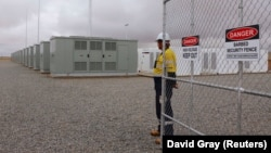 Робітник біля воріт Hornsdale Power Reserve, де встановлена батарея Tesla