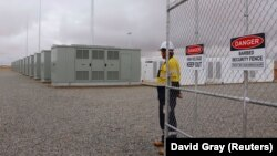 Рабочий у ворот Hornsdale Power Reserve, где установлена батарея Tesla.