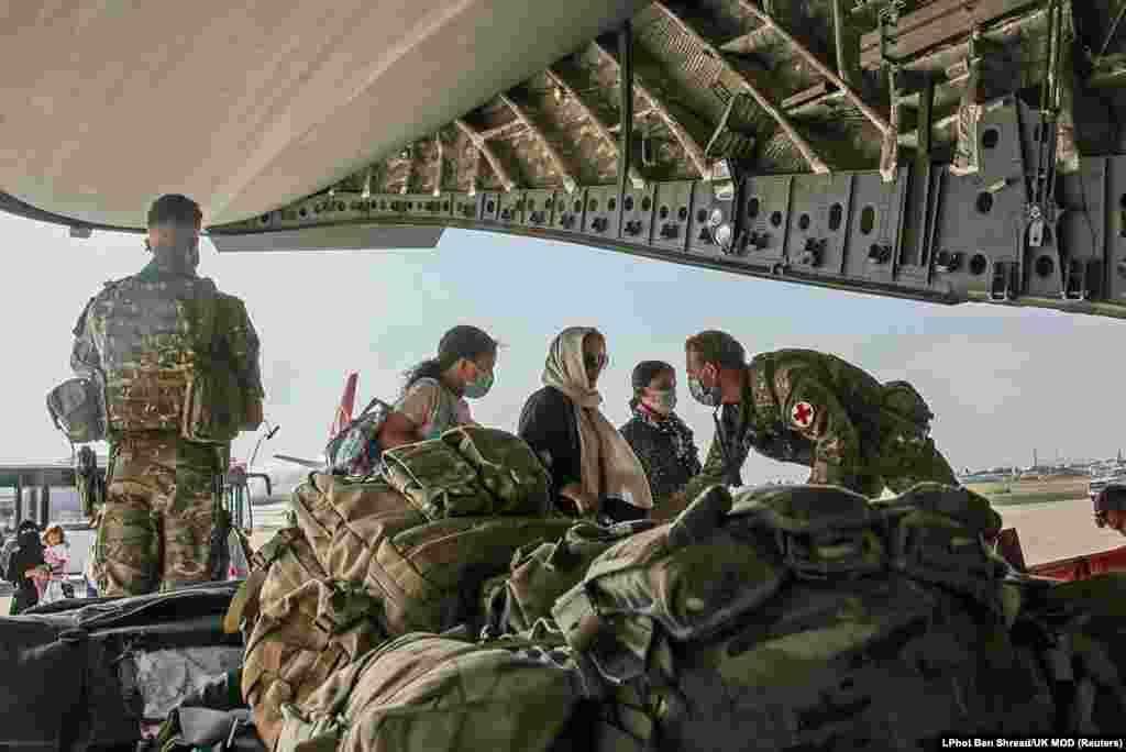 Граждане Великобритании и лица с двойным гражданством поднимаются на борт военного самолета во время эвакуации из кабульского аэропорта