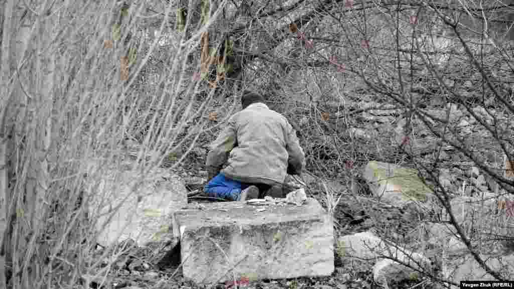Чоловік відкопує кабель для видобутку кольорових металів