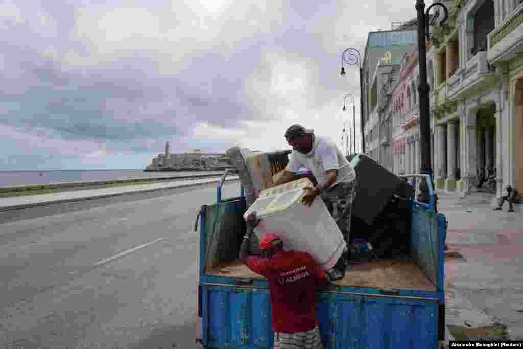 Helyiek rakodnak egy autó csomagtartójába - készülnek elhagyni Havannát a trópusi vihar előtt.
