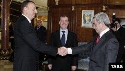 Попередню спробу відновити діалог щодо Нагірного Карабаху у 2012 році здійснила Росія: Алієв (ліворуч) і Сарґсян тиснуть руки в присутності тодішнього російського лідера Медведєва