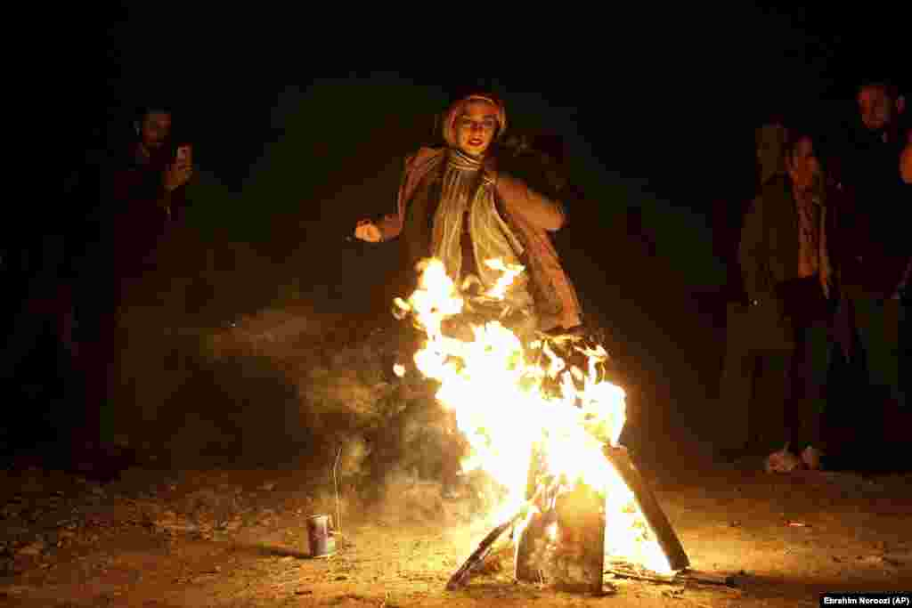 "An Iranian woman jumps over a bonfire during a celebration, known as ""Chaharshanbe Souri,"" or Wednesday Feast, marking the eve of the last Wednesday of the solar Persian year, in Tehran, Iran, Tuesday, March 19, 2019."