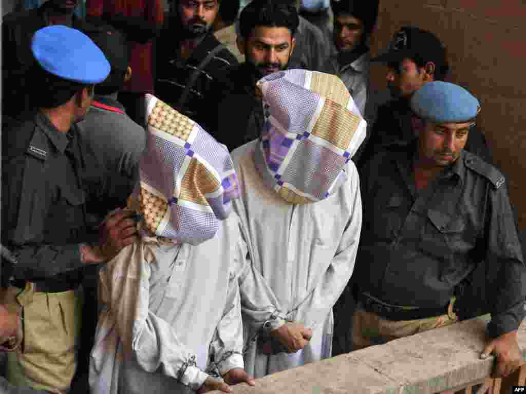 Pakistan -- Policemen escort two suspected members of the country's feared Tehrik-e-Taliban Pakistan (TTP) to a court room in Karachi, 20Oct2009 - PAKISTAN, Karachi : Pakistani policemen escort two suspected members of the country's feared Tehrik-e-Taliban Pakistan (TTP) to a court room in Karachi on October 20, 2009.