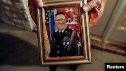 Wilburn Russell, 73, displays a portrait of his son, John M. Russell, the Army sergeant who was convicted of killing five fellow soldiers.