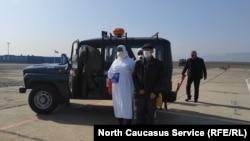 Участники учений по коронавирусу встречают самолет в аэропорту Махачкалы