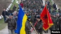 Українські вояки із прапорами і виконанням державного Гімну України на підході до російських військових, які відкрили попереджувальний вогонь. Бельбек, 4 березня 2014 року
