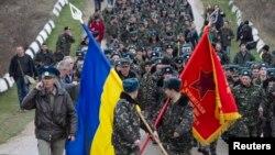 Українські військовослужбовці несуть прапори, аеропорт Бельбек, Крим, 4 березня 2014 року