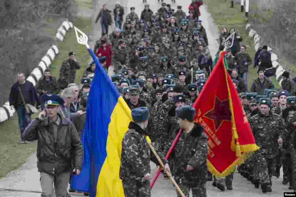 Ukrainian servicemen carry flags as they leave Belbek airport in the Crimea region on March 4, after confronting occupying Russian soldiers unarmed. (Reuters/Baz Ratner)