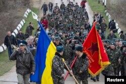 Українські вояки із прапорами і виконанням державного Гімну України на підході до російських військових, які відкрили попереджувальний вогонь. Крим, Бельбек, 4 березня 2014 року