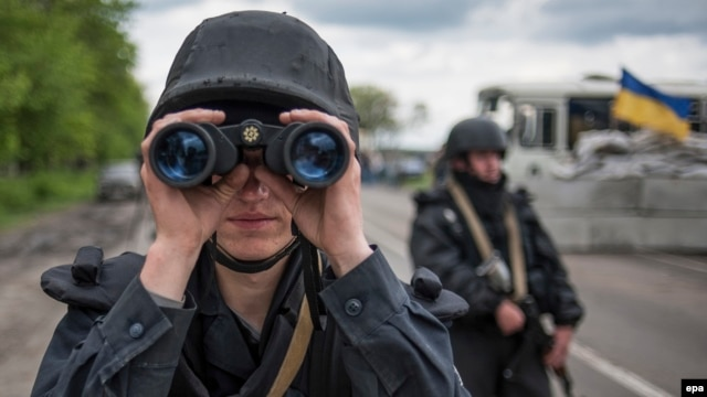 A Ukrainian soldier uses his binoculars at a checkpoint not far of Slovyansk on May 5.
