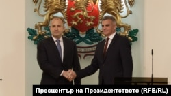 Bulgarian President Rumen Radev (left) and caretaker Prime Minister Stefan Yanev shake hands in Sofia after a new cabinet was sworn in on May 12.