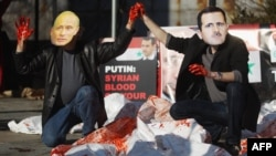 Actors wearing masks of Syrian President Bashar al-Assad and Russian Prime Minister Vladimir Putin perform with body bags during a demonstration outside UN headquarters on January 24.
