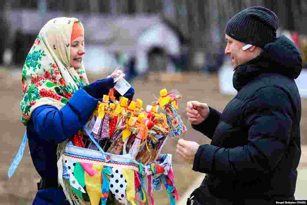 A woman selling effigies of winter during a celebration of Maslenitsa festival at the Etnomir (Ethnoworld) cultural and educational center in Kaluga region on March 1, 2020.