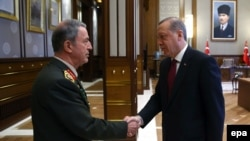 Turkish President Recep Tayyip Erdogan (right) greets the head of the Turkish Armed Forces General Staff, General Hulusi Akar, in Ankara in July.