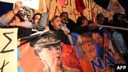 Posteri Angele Merkel i predsjednika Kipra Nikosa Anastasiadesa na protestima na Kipru