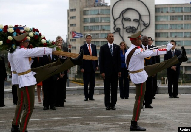 U.S. President Barack Obama (center) and U.S. Secretary of State John Kerry stand near an image of revolutionary hero Camilo Cienfuegos as they watch ceremonial guards during a wreath-laying ceremony at the Jose Marti monument on Revolutionary Square in Havana on March 21.