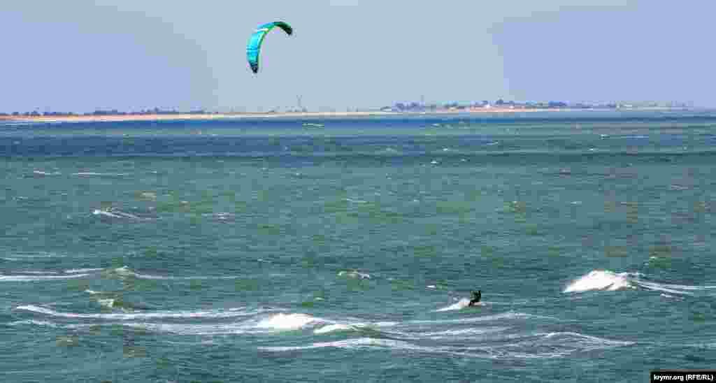 Один із двох кайтсерфінгістів ловить хвилю і вітер поблизу Кам'янського