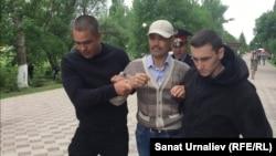 Сотрудники полиции задерживают 43-летнего бывшего полицейского Альбека Ергазиева, протестовавшего против своего увольнения. Уральск, 31 мая 2018 года.
