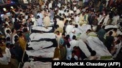 Pakistan -- Pakistani relatives gather around the bodies of blast victims after a suicide bomb attack near the Wagah border, November 2, 2014