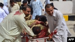 Pakistan -- Policemen carry an injured colleague into a hospital in Quetta, August 8, 2013