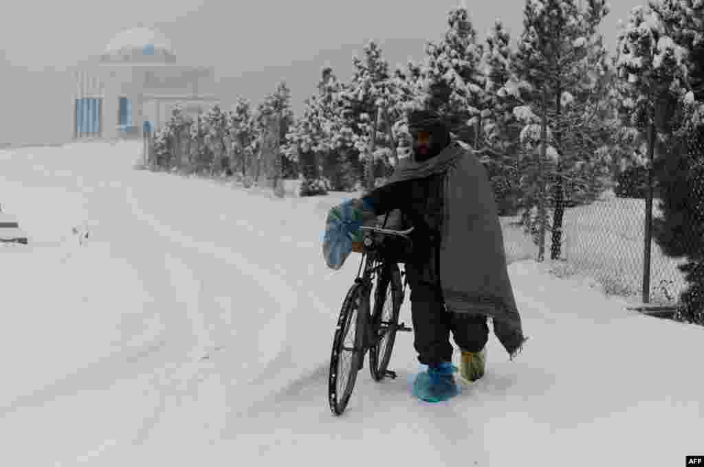 An Afghan man pushes his bicycle along a snow-covered road in Kabul. (AFP/Roberto Schmidt)