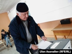 A voter in Bishkek casts his ballot into one of the new automatic ballot boxes.