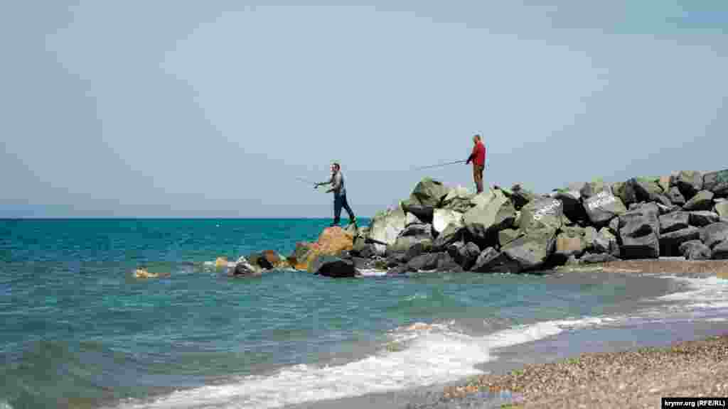 Двое мужчин рыбачат на«опасном» волнорезе из колотой скальной породы