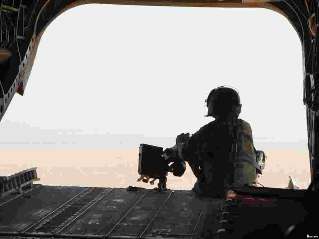 A U.S. soldier mans a machine gun at the rear of a U.S. military helicopter during a mission in Kandahar Province, southern Afghanistan, on October 1. Photo by Erik de Castro for Reuters
