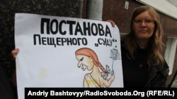 A Lutsenko supporter holds a placard that accuses the court of holding a staged production.