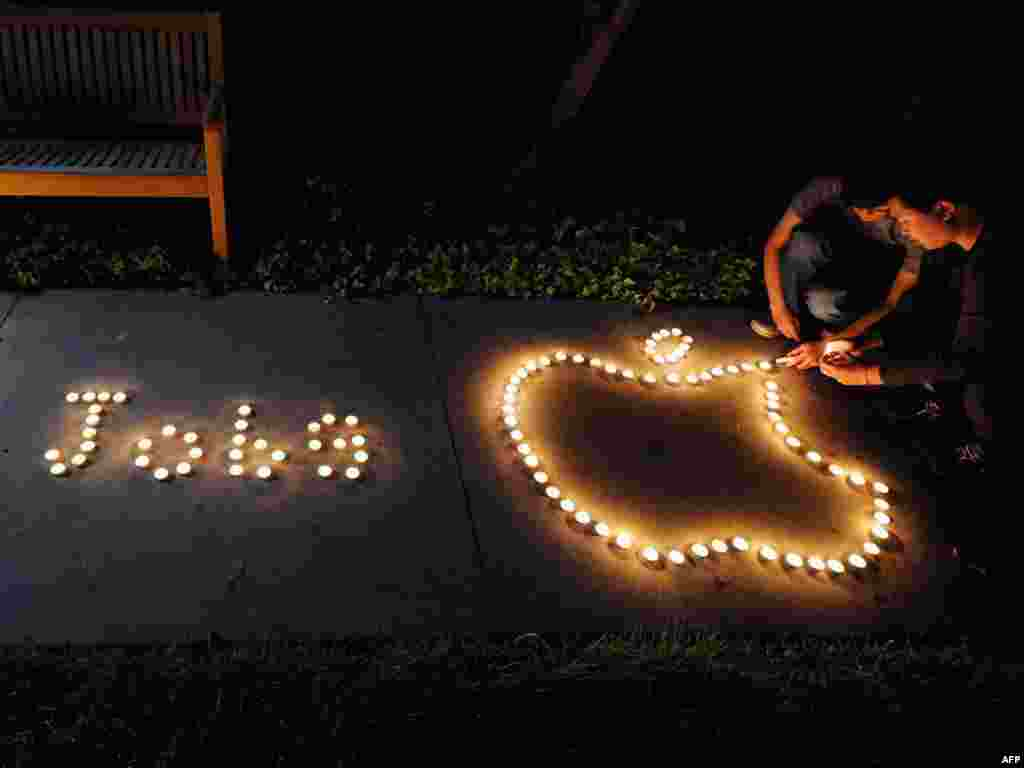 Chinese exchange students use candles to create the Apple logo and spell out the late CEO's name in a tribute in Cupertino, California, on October 5.