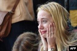 Молодая женщина во время поминальной акции у концертного зала «Батаклан», внутри которого террористы убили десятки людей. Париж, 15 ноября 2015 года.