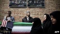 Iranians stand under anti-American posters as they attend a demonstration outside former U.S. Embassy in Tehran on November 4 depicting an American and Iranian negotiator sitting together.