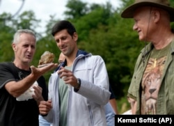 Osmanagic (right) watches Djokovic being shown a crystal in July, during the tennis star's first of two visits to Visoko.