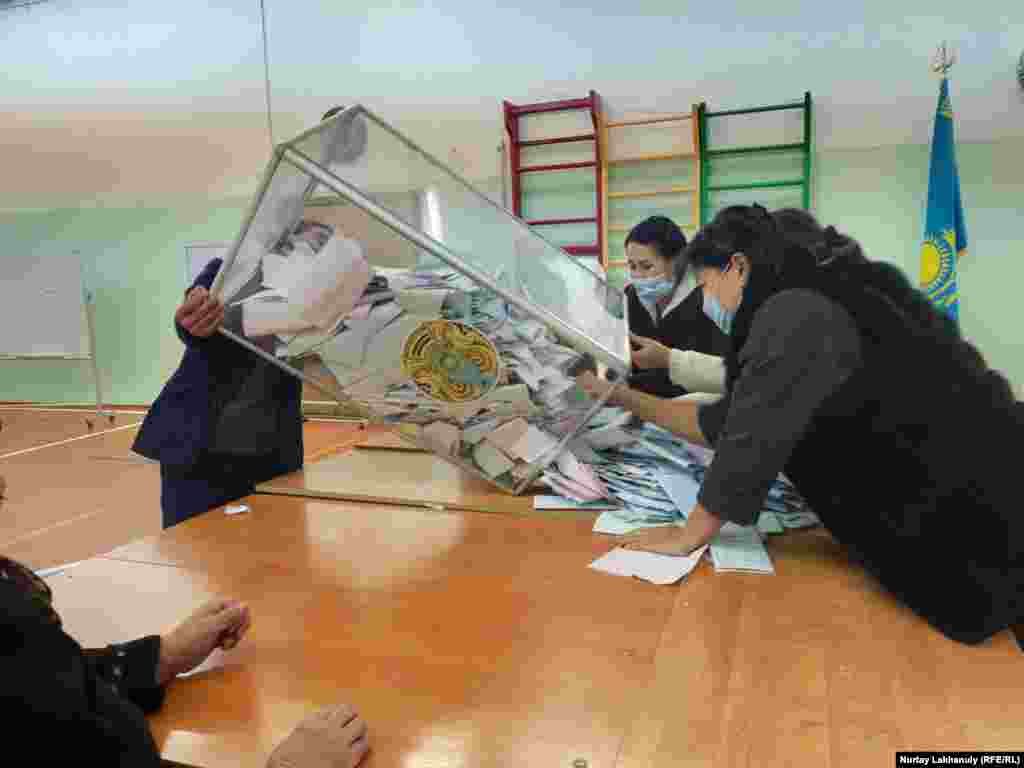 Members of a local election commission empty a ballot box ahead of counting votes after the elections in the village of Zhalgamys in the Almaty region on January 10.