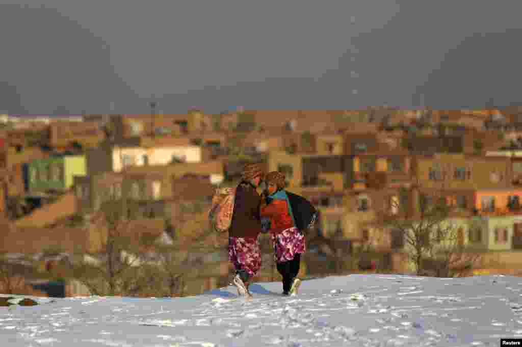 Afghan girls walk on snow as they head home in Kabul. (Reuters/Mohammad Ismail)