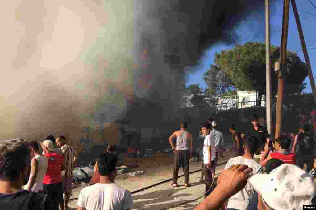 Migrantët duke shikuar zjarrin që përfshiu kampin Moria në Lesbos të Greqisë.