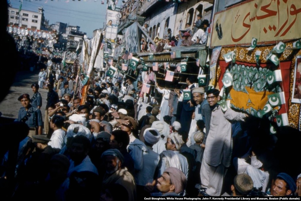 Crowds line a street in Peshawar to welcome the American first lady.