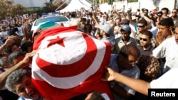 Mourners carry the coffin of slain opposition leader Muhammad Brahmi during his funeral procession in Tunis on July 27.