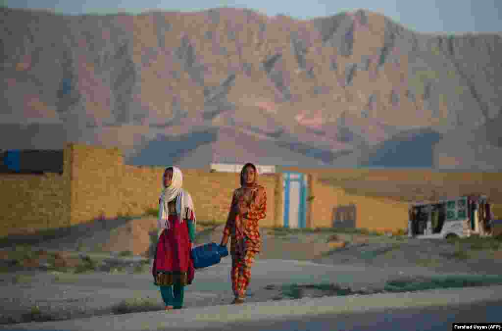 Afghan girls carry a gas canister on the outskirts of Mazar-e Sharif. (AFP/Farshad Usyan)