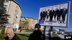 Ethnic Albanians walk past an electoral billboard featuring Serb leaders of the Independent Liberal Party in Pristina on December 8.