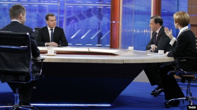 Russian Prime Minister Dmitry Medvedev (left) being interviewed by Russian TV channels