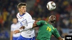 Еуропа чемпионаты іріктеуінде 12 гол салған футболшы Клаас-Ян Хунтелаар (сол жақта) Камерун ойыншысы Стефан Мбиаға қарсы ойнап жүр. Кейптаун, 24 маусым 2010 жыл.