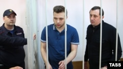 Defendants Aleksandr Margolin (right) and Ilya Guschin (center) stand in a cage during a hearing in the Bolotnaya case in a courtroom in Moscow in May.