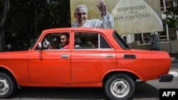 """На Кубе: советский автомобиль """"москвич"""" и плакат, приветствующий папу римского Франциска"""