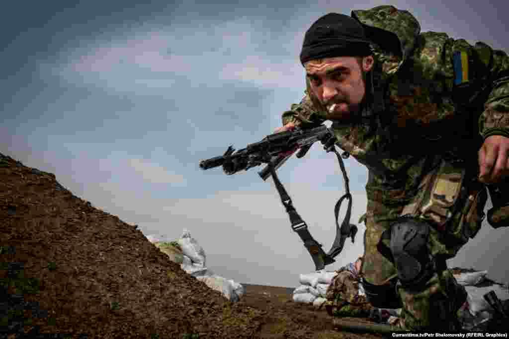 Боєць полку«Азов» намагається сховатися від шквального вогню противника. Село Широкино, 18 квітня 2015 року