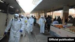 Специалисты в защитных костюмах проводят дезинфекцию на одном из рынков Узбекистана.