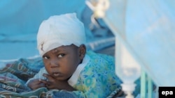 A child injured by the earthquake receives medical treatment at a makeshift hospital in Port-au-Prince on January 18.